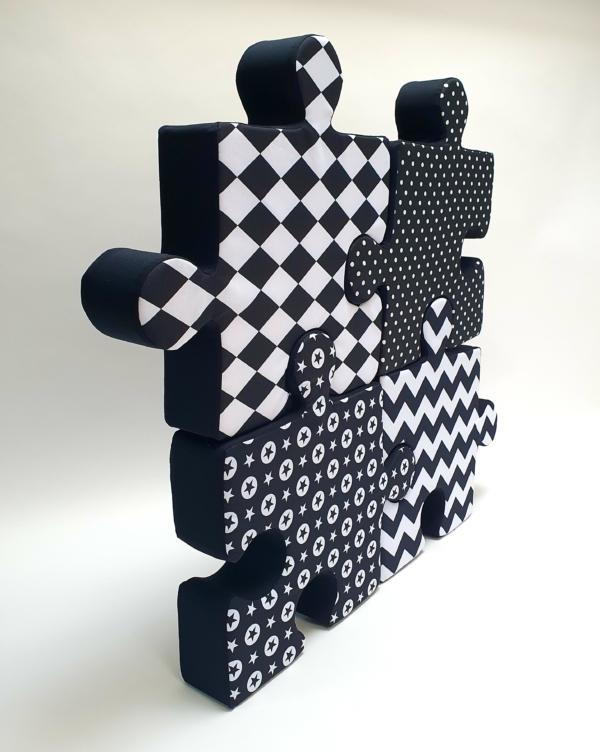 Cztery poduchopuzzle z kolekcji czarno - białej stoją na białym tle