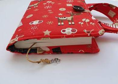 Ksiązka w okładce uszytej z czerwonego materiału w renifery