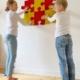 Dzieci układają na ścianie kolorowe puzzle