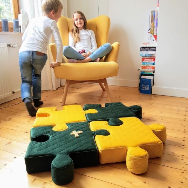 Mata puzzle ułożona z poduszek w kolorze musztardowym i butelkowej zieleni