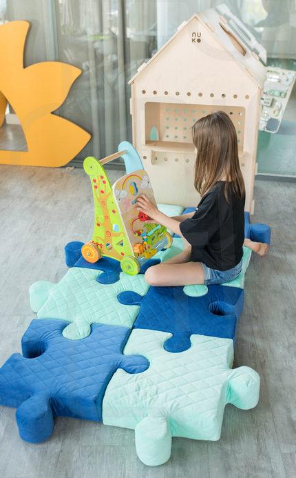 Granatowe poduchopuzzle w połączeniu z miętowymi ułożone jako mata dla dziewczynki do zabawy