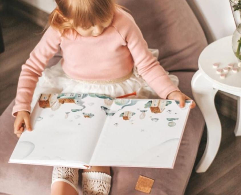 Dziewczynka siedzi na różowej pufie i czyta książeczkę