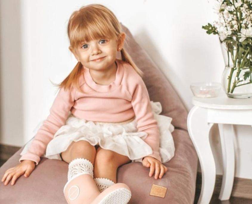 Dziewczynka siedzi na różowej pufie