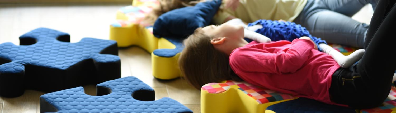 Dziewczyny leża na żółto - granatowych poduchopuzzlach i patrzą w okno.