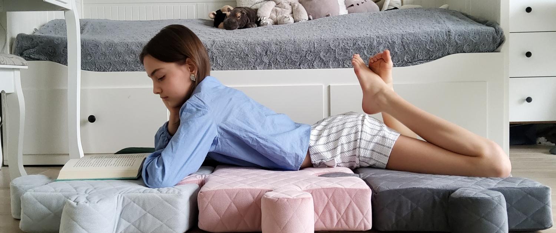 Dziewczyna leży na macie z poduchopuzzli i czyta książkę