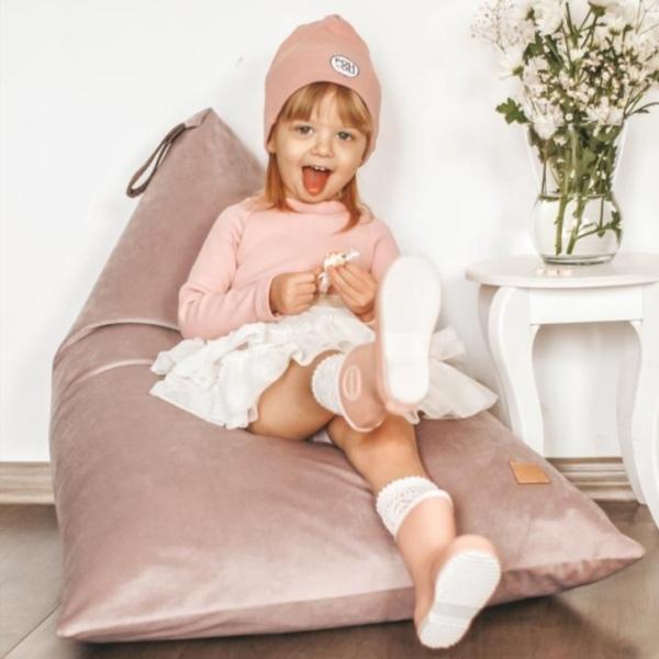Dziewczynka w kaloszach siedzi na różwej pufie
