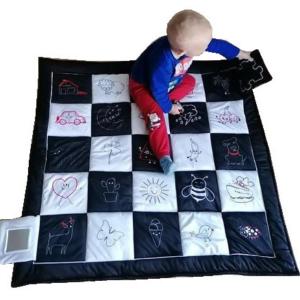 Dziecko chłopczyk siedzi na czarno-białej konrastowej macie sensorycznej i trzyma w rączce jej element