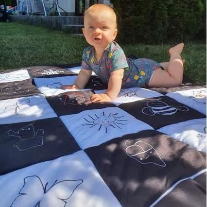 Małe dziecko leży na kontrastowej czarno - białej macie edukacyjnej na trawie