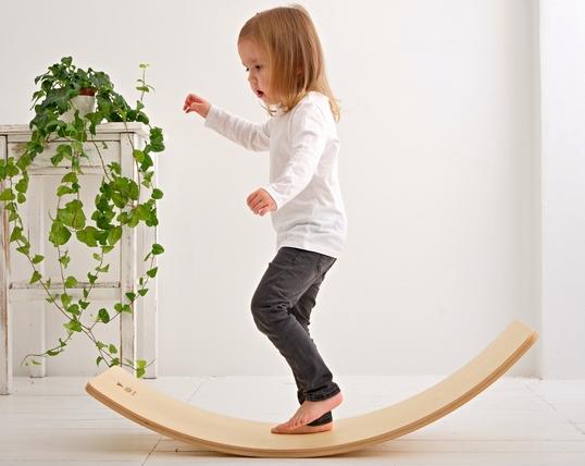 Dziewczynka bawi się na desce balansującej w kolorze brzozy