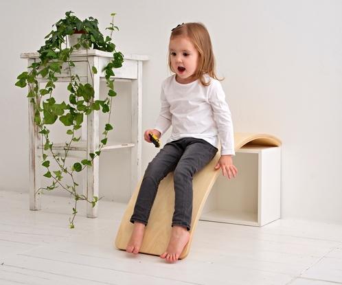 Dziewczynka używa deski balansującej jako zjeżdżalni