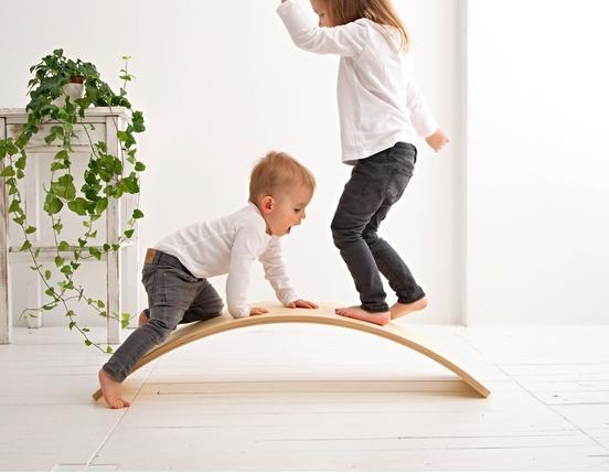Dzieci wspinają się na deskę do balansowania