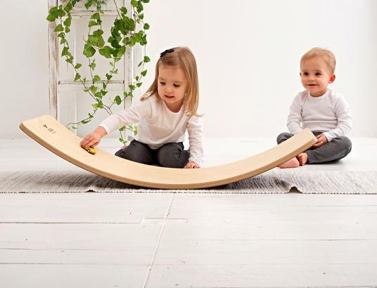 Dziewczynka bawi się samochodzikami na desce balansującej a z tyłu siedzi chłopczyk i się śmieje