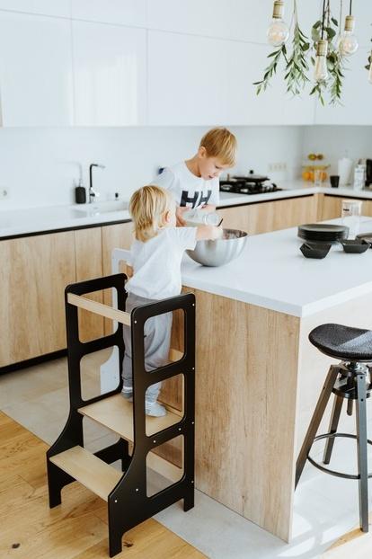 Chłopcy pomagają w kuchni stojąc na kitchen helperach