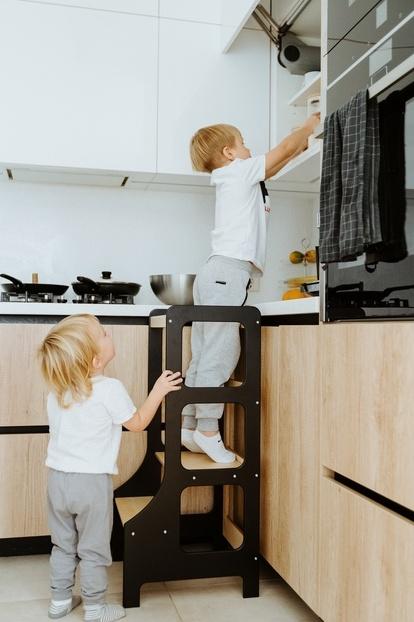 Chłopczyk sięga coś z wysokiej półki korzystając z wieży kuchennej w czarnym kolorze