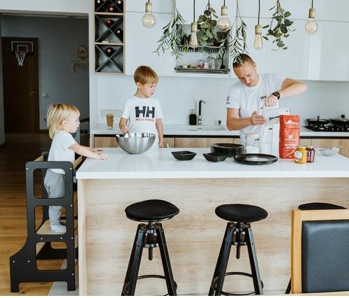 Chłopcy wspólnie z tatą przygotowują posiłek w kuchni stojąc przy blacie na kitchen helperach