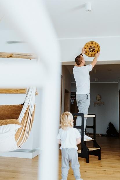 Mężczyzna wiesza zegar na ścianie stojąc na czarnej wieży kuchennej
