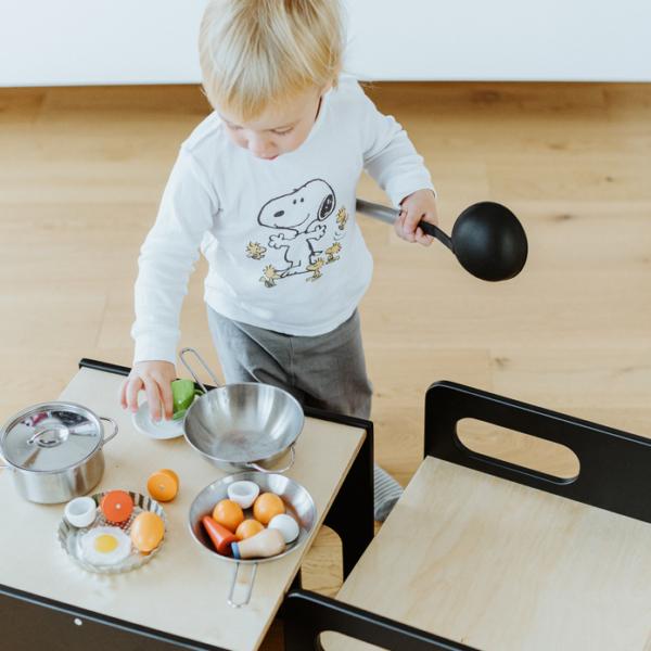 Chłopiec bawi się w gotowanie na stoliczku cube w czarnym kolorze