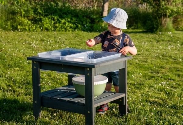 Stolik w szarym kolorze do zabawy sensorycznej w ogrodzie