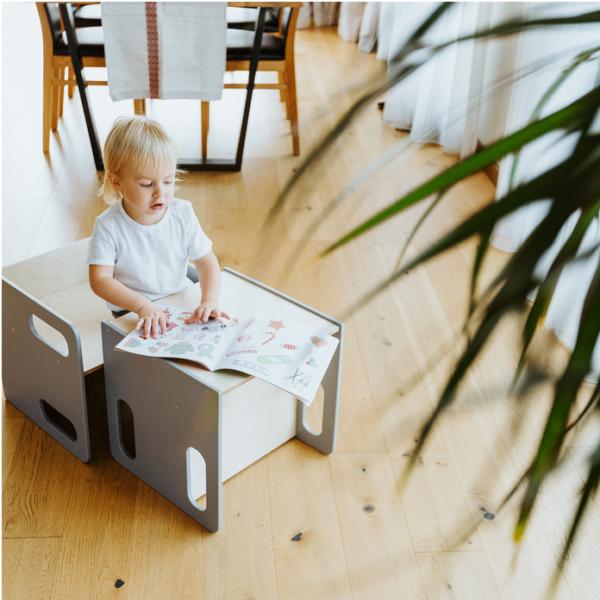 Chłopczyk siedzi na drewnianym krzesełku przy stoliczku montessori i się bawi