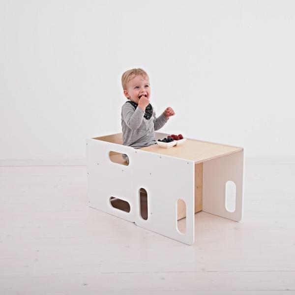 Chłopczyk je siedząc przy białym stoliczku cube w